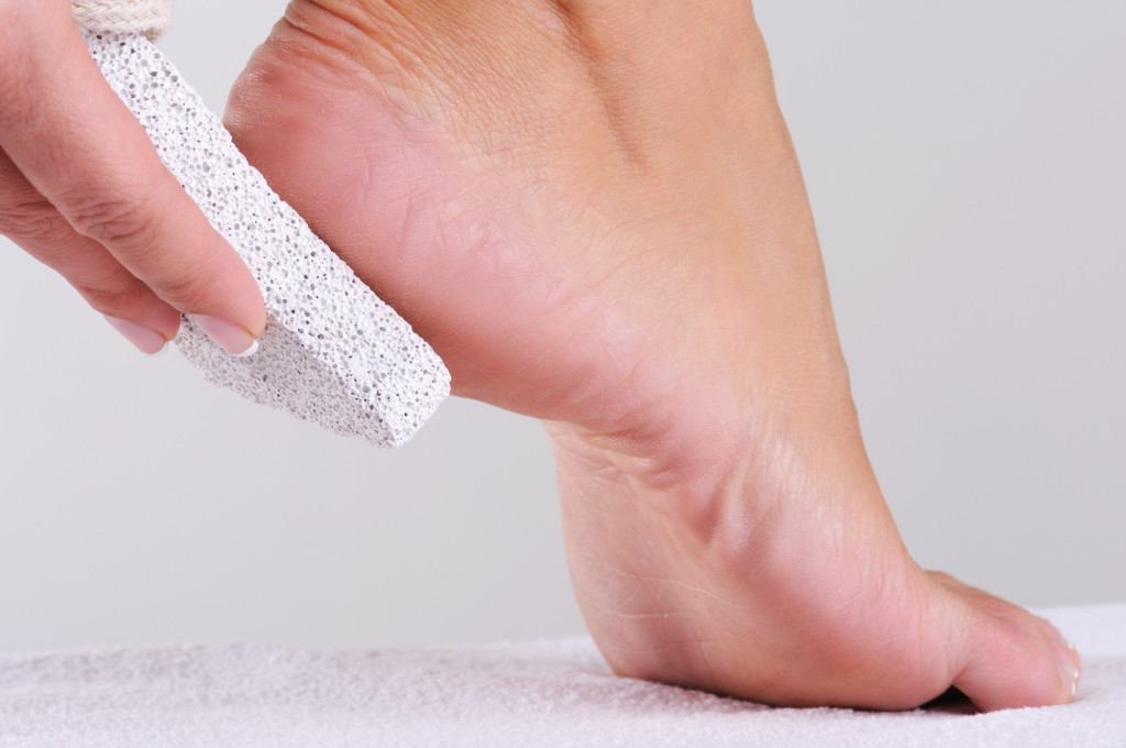 woman scrubbing foot by pumice
